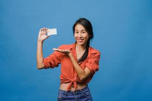junge asiatische Dame zeigt Kreditkarte mit positivem Ausdruck, lächelt breit, in Freizeitkleidung gekleidet, fühlt sich glücklich und steht einzeln auf blauem Hintergrund. Gesichtsausdruck Konzept. foto