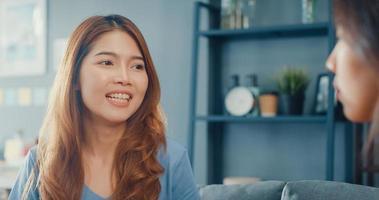 asiatische Hausfrauen mit ungezwungener Entspannung auf der Couch bei einer Tasse Tee sprechen zusammen über ihr Leben und ihren Ehemann-Beziehungsklatsch im Wohnzimmer im Haus. Mädchen Freunde Mitbewohner bleiben zusammen im Wohnheim. foto