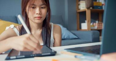 Junge asiatische Mädchen Teenager mit gelegentlichem Gebrauch von Computer-Laptop-Fokus, um online zu lernen, Vorlesung in digitalem Laptop im Wohnzimmer zu Hause zu schreiben. Isolieren Sie das Online-E-Learning-Konzept für die Coronavirus-Pandemie. foto
