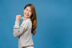 Porträt einer jungen asiatischen Dame, die mit fröhlichem Ausdruck lächelt, zeigt etwas Erstaunliches an leeren Stellen in Freizeitkleidung und steht einzeln auf blauem Hintergrund. Gesichtsausdruck Konzept. foto