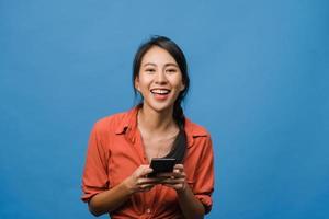 überraschte junge asiatische dame, die handy mit positivem ausdruck benutzt, breit lächelt, in lässiger kleidung gekleidet ist und die kamera auf blauem hintergrund betrachtet. glückliche entzückende frohe frau freut sich über erfolg. foto
