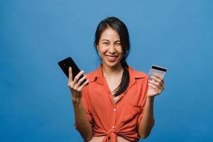 junge asiatische Dame mit Telefon- und Kreditkarte mit positivem Ausdruck, lächelt breit, in Freizeitkleidung gekleidet und steht einzeln auf blauem Hintergrund. glückliche entzückende frohe frau freut sich über erfolg. foto