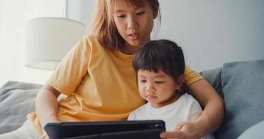 Fröhliche, fröhliche Asien-Familienmutter und süßes Kind mit digitalem Tablet-Interesse-Cartoon und Film ansehen, der Spaß auf der Couch im Wohnzimmer im Haus hat. Zeit miteinander verbringen, Quarantäne wegen Coronavirus. foto