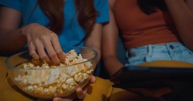 Attraktive asiatische Damen mit Casual genießen glücklichen Moment Fokus Online-Filmunterhaltung auf Tablet essen Popcorn-Site auf der Couch Wohnzimmer in der Nacht zu Hause Quarantänekonzept für Lifestyle-Aktivitäten. foto