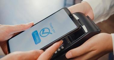 junge asiatische weibliche Self-Service-Benutzung Mobiltelefon kontaktlos mit Kreditkartenlesegerät im Café-Restaurant bezahlen. Inhaber Kleinunternehmen, bargeldlose Technologie und Geldtransferkonzept. Nahaufnahme. foto