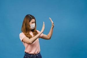 Junge asiatische Dame trägt eine medizinische Gesichtsmaske, die aufhört, mit der Handfläche mit negativem Ausdruck zu singen und die Kamera einzeln auf blauem Hintergrund ansieht. soziale Distanzierung, Quarantäne wegen Corona-Virus. foto
