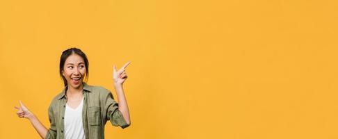 Porträt einer jungen asiatischen Dame, die mit fröhlichem Ausdruck lächelt, zeigt etwas Erstaunliches an leeren Stellen in Freizeitkleidung und steht einzeln auf gelbem Hintergrund. Panoramabanner mit Kopienraum. foto