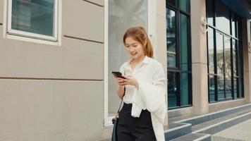 erfolgreiche junge asiatische Geschäftsfrau in modischer Bürokleidung mit Smartphone und Eingabe von Textnachrichten, während sie morgens allein im Freien in der urbanen modernen Stadt spaziert. Business-on-Go-Konzept. foto