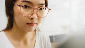 freiberufliche junge asiatische Geschäftsfrau Freizeitkleidung mit Laptop im Wohnzimmer zu Hause arbeiten. Arbeiten von zu Hause aus, Fernarbeit, Selbstisolierung, soziale Distanzierung, Quarantäne zur Vorbeugung von Coronaviren. foto