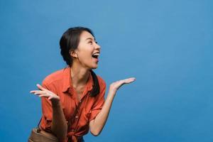 junge asien dame fühlen sich glücklich mit positivem ausdruck, freudige überraschung funky, gekleidet in lässiges tuch einzeln auf blauem hintergrund. glückliche entzückende frohe frau freut sich über erfolg. Gesichtsausdruck. foto