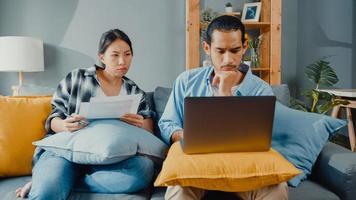 Asien junges paar mann und frau sitzen auf der couch ernsthafter fokus auf laptop-computer überprüfen dokumentpapier zahlen rechnungen online planen budgetausgaben im wohnzimmer. junges verheiratetes asiatisches schuldendarlehensproblemkonzept. foto