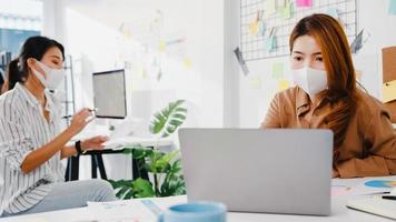 asiatische Geschäftsleute, die Computerpräsentationen verwenden, Brainstorming-Ideen über neue Projektkollegen und tragen eine schützende Gesichtsmaske im neuen normalen Büro. Lebensstil und Arbeit nach dem Coronavirus. foto