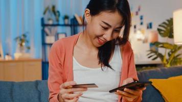 Nachtzeit schöne lächelnde asiatische Dame verwenden Handy bestellen Online-Shopping-Produkt mit Kreditkarte auf dem Sofa im Wohnzimmer. zu Hause bleiben, Selbstquarantäneaktivität, lustige Aktivität für Covid-Quarantäne. foto