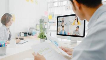 asiatische Geschäftsleute, die Desktop verwenden, sprechen mit Kollegen, die ein Geschäfts-Brainstorming über den Plan in einem Videoanruf-Meeting in einem neuen normalen Büro diskutieren. Lebensstil soziale Distanzierung und Arbeit nach dem Coronavirus. foto