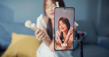 Fröhliche junge asiatische Mädchen Make-up Vlogger vor der Telefonkamera genießen Review-Gespräch mit dem Publikum im Wohnzimmer im Haus. Konzept der Coronavirus-Pandemie mit sozialer Distanz. Freiheit und aktives Lifestyle-Konzept. foto