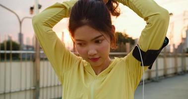 glückliche junge asiatische Sportlerin in gelber Kleidung, die sich auf das Training im städtischen Umfeld vorbereitet. Koreanisches Teenie-Mädchen, das sich Pferdeschwanzhaare bindet und sich vor ihrem Training auf der Gehwegbrücke am frühen Morgen fertig macht foto