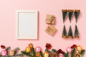 minimale kreative flache Lage der traditionellen Winterweihnachtskomposition und der Neujahrsferienzeit. Draufsicht Mockup schwarze Bilderrahmen für Text auf rosa Hintergrund. Mock-up und kopieren Sie Raumfotografie. foto