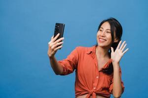 Lächelnde entzückende asiatische Frau, die Selfie-Foto auf Smartphone mit positivem Ausdruck in Freizeitkleidung macht und auf blauem Hintergrund steht. glückliche entzückende frohe frau freut sich über erfolg. foto