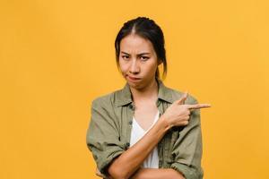 junge asiatische Dame zeigt etwas Erstaunliches an Leerzeichen mit negativem Ausdruck, aufgeregtem Schreien, weinen emotional wütenden Blick auf die Kamera einzeln auf gelbem Hintergrund. Gesichtsausdruck Konzept. foto