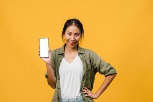 junge asiatische Dame zeigt leeren Smartphone-Bildschirm mit positivem Ausdruck, lächelt breit, gekleidet in Freizeitkleidung und fühlt sich glücklich auf gelbem Hintergrund. Handy mit weißem Bildschirm in weiblicher Hand. foto