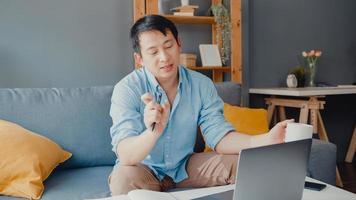 Junger asiatischer Geschäftsmann, der Laptop verwendet, spricht mit Kollegen über den Plan im Videoanruf, während er von zu Hause aus im Wohnzimmer arbeitet. Selbstisolation, soziale Distanzierung, Quarantäne zur Vorbeugung des Coronavirus. foto