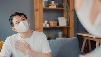 Junge asiatische Ärztin trägt Gesichtsmaske mit digitaler Tablette, die gute Gesundheitstestnachrichten mit glücklichen männlichen Patienten teilt, die auf der Couch im Haus sitzen. Krankenversicherung, besuchen Sie den Patienten zu Hause Konzept. foto