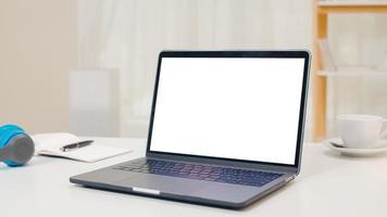 Mock-up-Laptop mit weißem Bildschirm, der auf dem Schreibtisch im gemütlichen Wohnzimmer eines modernen Zuhauses steht. foto