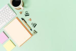 kreatives flaches Laienfoto des Arbeitsplatzschreibtisches. Schreibtisch von oben mit Tastatur und offenem Mockup-Schwarz-Notizbuch auf pastellgrünem Hintergrund. Draufsichtmodell mit Kopienraumfotografie. foto