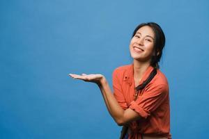 Porträt einer jungen asiatischen Dame, die mit fröhlichem Ausdruck lächelt, zeigt etwas Erstaunliches an leeren Stellen in legerem Tuch und blickt auf die Kamera einzeln auf blauem Hintergrund. Gesichtsausdruck Konzept. foto