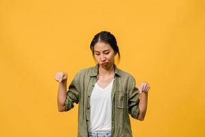 Junge asiatische Dame zeigt etwas Erstaunliches im leeren Raum mit negativem Ausdruck, aufgeregtem Schreien, weinen emotional wütend in Freizeitkleidung einzeln auf gelbem Hintergrund. Gesichtsausdruck Konzept. foto