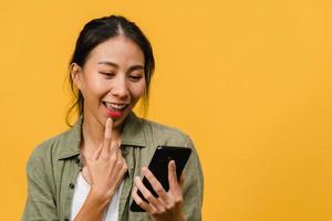 junge asiatische dame, die telefon mit positivem ausdruck verwendet, breit lächelt, in lässiger kleidung gekleidet fühlt sich glücklich und steht einzeln auf gelbem hintergrund. glückliche entzückende frohe frau freut sich über erfolg. foto