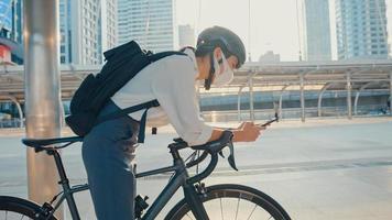 Asiatische Geschäftsfrau trägt Rucksack, trägt eine Antivirenschutzmaske, macht einen Fahrradspaziergang und überprüft das Telefon in der Stadtstraße, um im Büro zu arbeiten. zur Arbeit pendeln, Berufspendler für das Covid-19-Konzept. foto