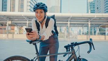 Lächeln Sie asiatische Geschäftsfrau mit Rucksack, die eine Smartphone-Look-Kamera im Stadtstand an der Straße mit dem Fahrrad verwendet, um im Büro zu arbeiten. Sportmädchen benutzen Telefon für die Arbeit. zur Arbeit pendeln, Berufspendler in der Stadt. foto