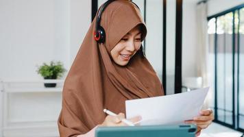 asiatische muslimische dame tragen kopfhörer mit digitaler tablette sprechen mit kollegen über verkaufsbericht in konferenz-videoanrufen, während sie von zu hause in der küche arbeiten. soziale Distanzierung, Quarantäne wegen Corona-Virus. foto