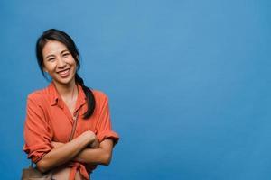 Porträt der jungen asiatischen Dame mit positivem Ausdruck, verschränkten Armen, breitem Lächeln, in Freizeitkleidung gekleidet und mit Blick auf die Kamera auf blauem Hintergrund. glückliche entzückende frohe frau freut sich über erfolg. foto