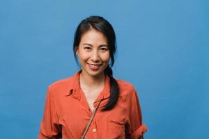 junge asiatische Dame mit positivem Ausdruck, breit lächeln, in Freizeitkleidung gekleidet und mit Blick auf die Kamera auf blauem Hintergrund. glückliche entzückende frohe frau freut sich über erfolg. Gesichtsausdruck Konzept. foto