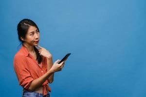 junge asiatische dame, die telefon mit positivem ausdruck verwendet, breit lächelt, in lässiger kleidung gekleidet fühlt sich glücklich und steht einzeln auf blauem hintergrund. glückliche entzückende frohe frau freut sich über erfolg. foto