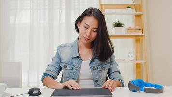 Porträt von freiberuflichen Smart Business Women Casual Wear mit Laptop am Arbeitsplatz im Wohnzimmer zu Hause arbeiten. glückliche junge asiatische mädchen entspannen sich auf dem schreibtisch suchen und arbeiten im internet. foto