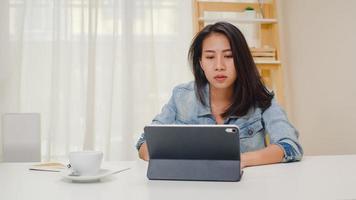 frustrierte junge asiatische Dame, die ein Problem mit dem nicht funktionierenden Tablet-Computer hat, der auf dem Schreibtisch sitzt. Freiberufliche Smart Business Women Casual Wear mit Tablet am Arbeitsplatz im Wohnzimmer im Home Office. foto