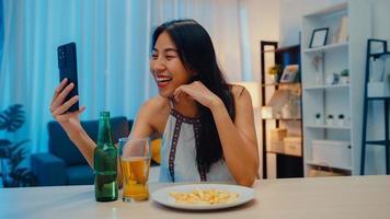 junge asiatische dame trinkt bier und hat spaß fröhliche momentnacht party neujahrsveranstaltung online feier per videoanruf per telefon zu hause nachts. soziale Distanzierung, Quarantäne zur Coronavirus-Prävention. foto