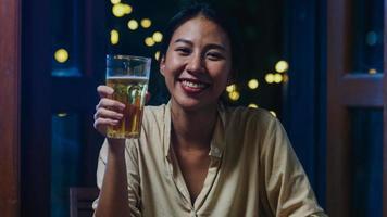 junge asiatische dame trinkt bier und hat spaß fröhliche nacht party neujahrsveranstaltung online feier per videoanruf per telefon zu hause nachts. soziale Distanz, Quarantäne für Coronavirus. Standpunkt oder Standpunkt foto