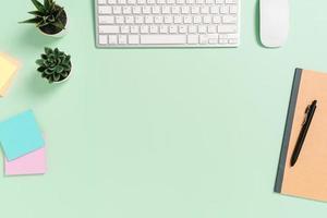 minimaler arbeitsplatz - kreatives flaches foto des arbeitsplatzes. Schreibtisch von oben mit Tastatur, Maus und Buch auf pastellgrünem Hintergrund. Draufsicht mit Kopienraum, Flachfotografie.