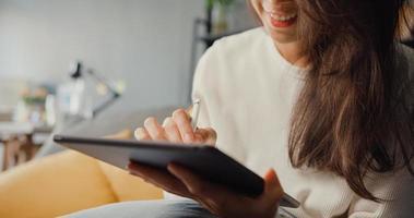 Nahaufnahme freiberufliche Asia Lady Freizeitkleidung mit Tablet online lernen im Wohnzimmer zu Hause. Arbeit von zu Hause, Remote-Arbeit, Fernunterricht, soziale Distanz, Quarantäne zur Vorbeugung des Coronavirus. foto