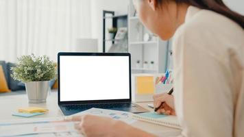 Junge Geschäftsfrau in Asien verwendet ein Smartphone mit leerem weißem Bildschirm für Werbetexte, während sie von zu Hause aus im Wohnzimmer arbeitet. Chroma-Key-Technologie, Marketing-Design-Konzept. foto