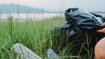 glückliche junge asien-aktivisten sammeln plastikmüll im wald. koreanische freiwillige Helferinnen helfen, die Natur sauber zu halten und Müll aufzusammeln. Konzept über Umweltverschmutzung Probleme. foto