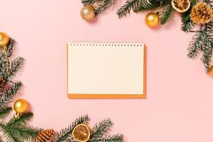 minimale kreative flache Lage der traditionellen Winterweihnachtskomposition und der Neujahrsferienzeit. Ansicht von oben offenes Mockup schwarzes Notizbuch für Text auf rosa Hintergrund. Mock-up und kopieren Sie Raumfotografie. foto