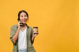 junge asiatische dame telefoniert und hält kaffeetasse mit positivem ausdruck, lächelt breit, gekleidet in lässiges tuch, fühlt sich glücklich und steht einzeln auf gelbem hintergrund. Gesichtsausdruck Konzept. foto