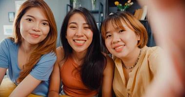 Teenager asiatische Frauen fühlen sich glücklich lächelndes Selfie und schauen auf die Kamera, während sie sich zu Hause im Wohnzimmer entspannen. fröhliche Mitbewohnerinnen Videoanruf mit Freund und Familie, Lifestyle-Frau zu Hause Konzept. foto