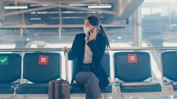 Smart Asian Business Girl Wear Suit sitzt mit Koffer in Bankanruf Smartphone-Gespräch mit Partner warten auf den Flug am Flughafen. Geschäftsreisender Pendler in Covid-Pandemie, Geschäftsreisekonzept. foto