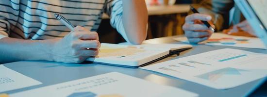 Asien-Geschäftsleute treffen Plananalysestatistiken Brainstorming und Header des Teams halten Tablet-Diagramm und Mitarbeiter nehmen in der Home-Office-Nacht zur Kenntnis. Panorama-Banner-Hintergrund mit Kopienraum. foto